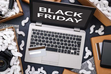 Black Friday and big sale in electronics store concept. Laptop and credit card surrounded by cardboard boxes with protective foam pads and electronic products inside. Flat lay