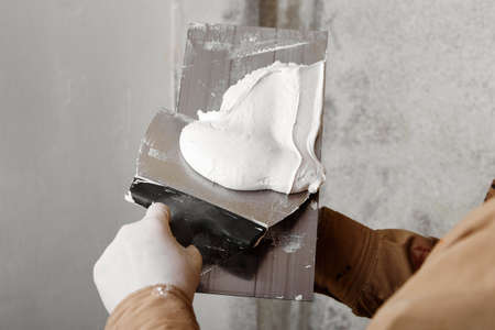 Construction worker with trowel and putty knife plastering a wall. House renovation concept.