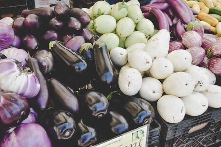 eggplants in a market, purple and green colors. the fruit of the plant is used in cooking in different cuisines, and is considered a vegetable, even though it is the berry
