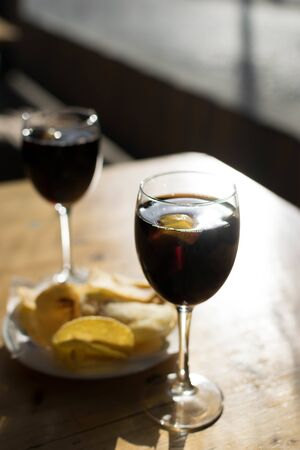 two cups of vermouth in a sunny day and a plate of potato chips.