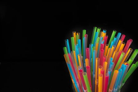 Isolated group of plastic straws in colors on a black background with space for copy text. Party concept 스톡 콘텐츠