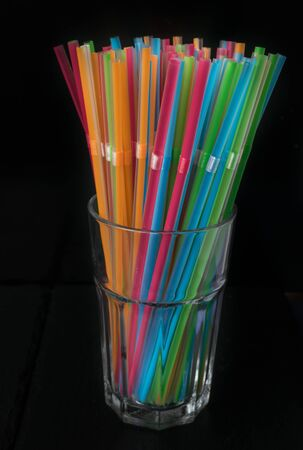 Isolated group of plastic colored straws in a glass on a black background. 스톡 콘텐츠