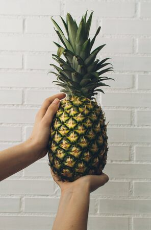 hands of a girl holding a pineapple.