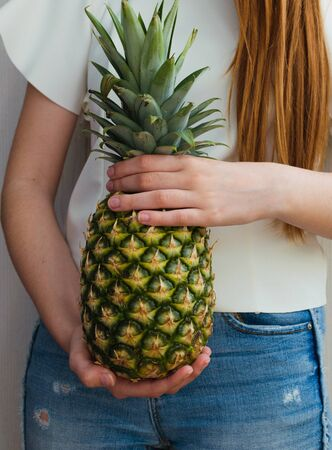 healthy girl with long red hair holding a pineapple 스톡 콘텐츠