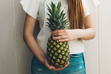 healthy slim girl with long red hair holding a pineapple. summer diet concept