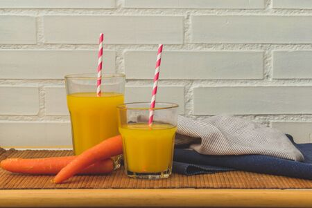 two glasses of orange and carrot juice with paper straws and space for text 스톡 콘텐츠