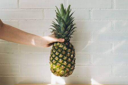 girl arm holding a pineapple in a sunny space for copy text