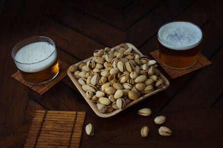 bowl full of pistachios and beer in a pub