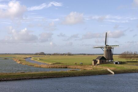 Landscape of the Dutch island Texel with a windmill, horses, a blue sky and white clouds Stock Photo