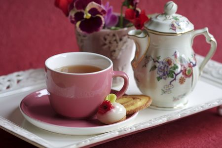 tea-cup and tea-pot on a tray with cookies and a little vase with flowers