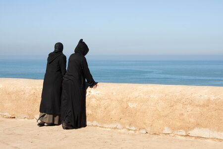 Two Moroccan women in black abayas looking out over the Atlantic ocean in Rabat, Morocco