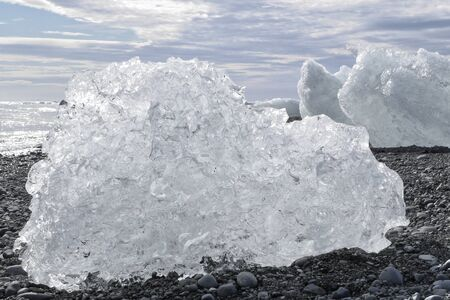 Large chunks of ice on a black stone beach in Iceland