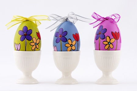 three hand painted easter eggs in egg-cups