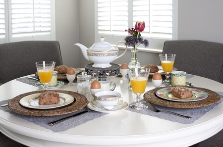 Dining table nicely laid for breakfast with sandwiches, eggs and orange juice in a brightly lit room