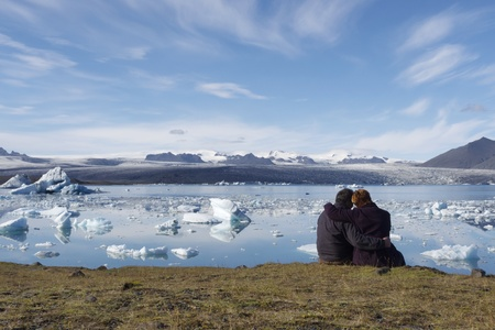 Two people enjoying the view of icebergs in Jokulsarlon, Iceland