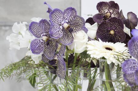 Several little vases with dappled orchids, roses and gerberas photo
