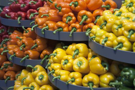 Shelves piled with red, orange, yellow and green peppers