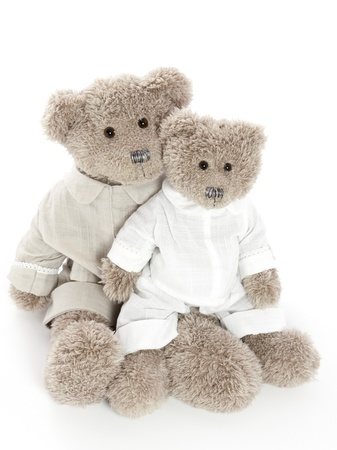 Two teddybears sitting closely together