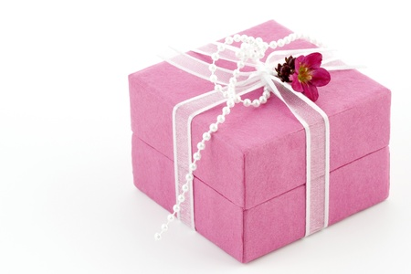 Beautiful pink gift box with a ribbon, a little flower and pearls