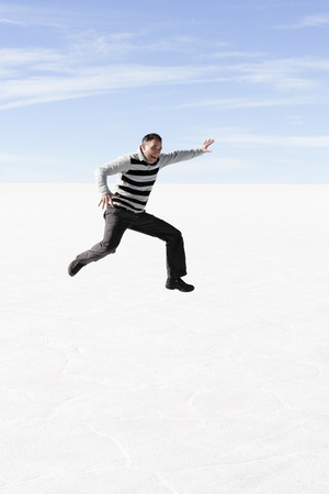Man jumping in the air at the salt lake in Bolivia
