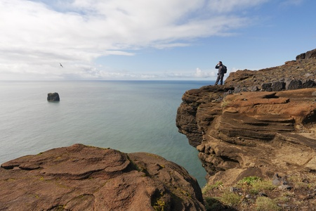 A beautiful seascape with a man standing on red rocks and watching the ocean in Iceland Stock Photo