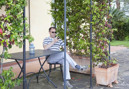 Man checking his mobile phone on a terrace with creepers in Tuscany
