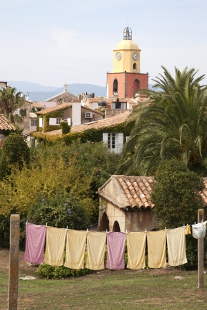 view of the church in Saint-Tropez with a clothesline and colorful towels