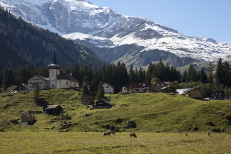 Typical Swiss village at a sunny day with snow on the mountains  Stock Photo