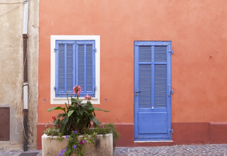 French wooden door and window in an orange wall Stock Photo
