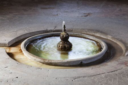 Old fountain in the garden of Royal Palace Real Alcazar in Sevilla, Spain