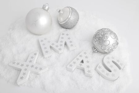 XMAS, white wooden letters in the snow and christmas balls Stock Photo