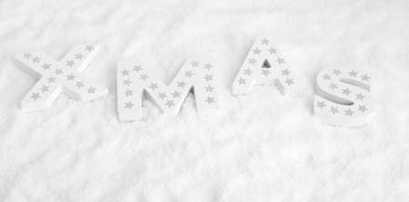 White wooden letters in snow form the word XMAS with silver stars
