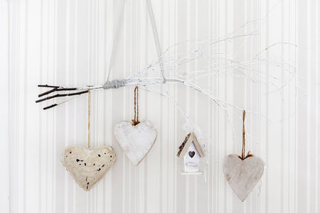 Hearts and a birdhouse hanging on white branches