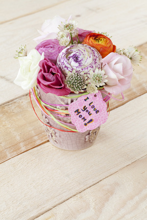 Beautiful bouquet of spring flowers in flowerpot and a card with the text  I love you Mom  photo