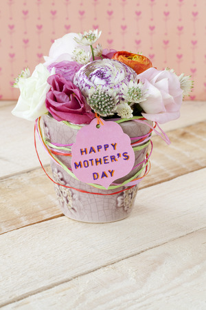 Beautiful bouquet of spring flowers in a flowerpot on a wooden table, for Mother