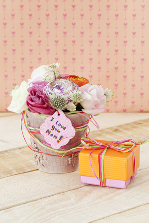 Beautiful bouquet of flowers in flowerpot and a gift box for Mother