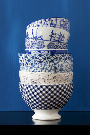 Stack of porcelain bowls with blue and white designs Stock Photo