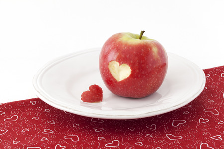 Red apple with a heart shaped cut-out on a tablecloth Stock Photo