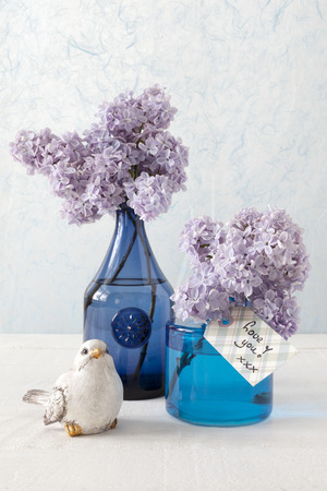 mother'sday: Still life with Lilacs in blue vases, a little bird and a card with the words  Love you Stock Photo