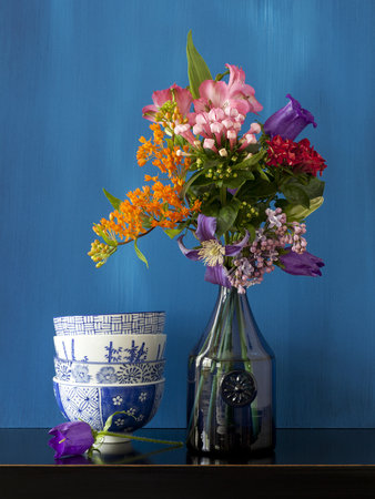 Beautiful still life with flowers in a vase and some bowls on a black table
