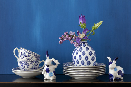 Still life with blue and white dishes, porcelain bunnies and flowers in a little vase Stock Photo