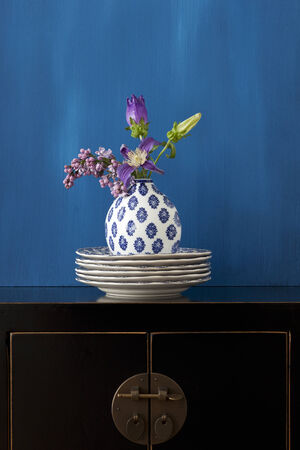 Still life with a black Chinese cabinet and flowers in a little vase Stock Photo