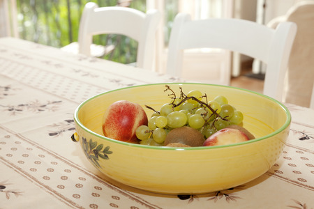 Fruit bowl with grapes, peaches and kiwi fruit on a table Stock Photo