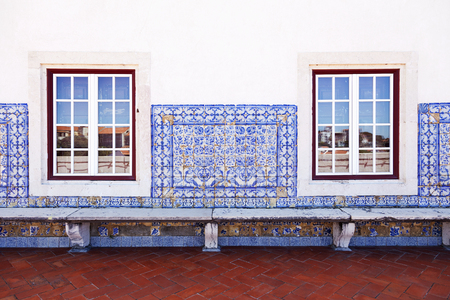 Wall with old Portuguese tiles, windows and a bench
