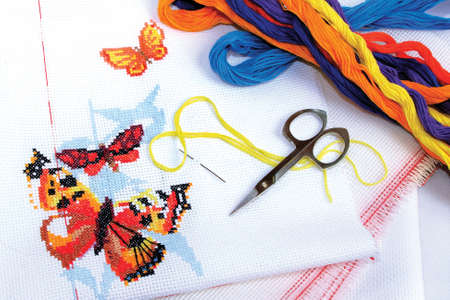 Multicolored butterflies embroidered cross-stitch, canvas for embroidery, threads of floss Stock Photo