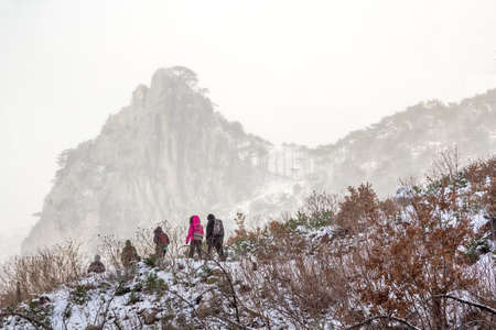 A group of tourists on a winter walk in the high mountains Stock Photo