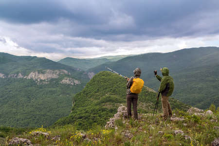 Two tourists photographed landscape in the mountains in the rain Stock Photo