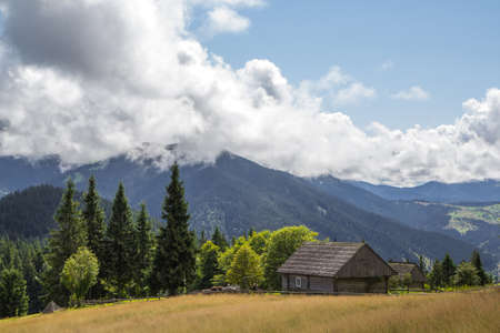 Mountain landscape with an old wooden house in the Carpathian forests