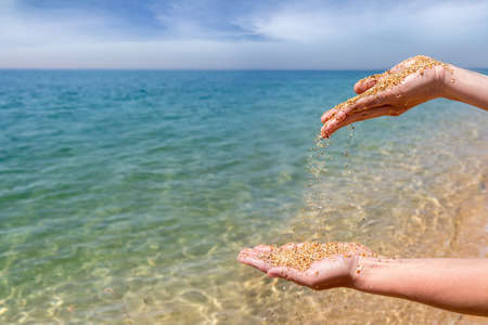 Hands pouring coral sand on the sea background
