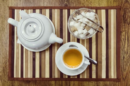 Top view of a cup of green tea, teapot and sugar bowl on a wooden background